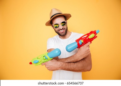 Image of happy young man standing isolated over yellow background. Looking at camera holding toy water guns.