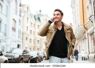 Image of happy young man walking on the street and looking aside while talking by his phone.