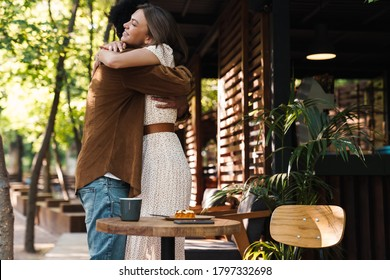 Image of happy young multinational couple hugging and smiling while drinking coffee in cafe outdoors