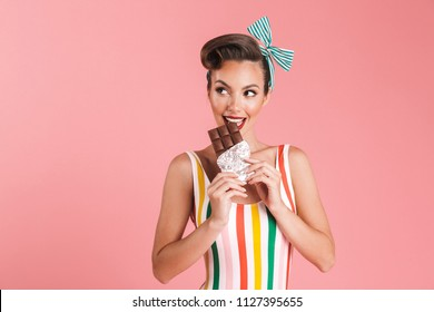 Image of happy young pin up woman isolated over pink wall background eating chocolate.