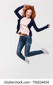 Image of happy young redhead lady jumping isolated over white wall background. Looking camera.