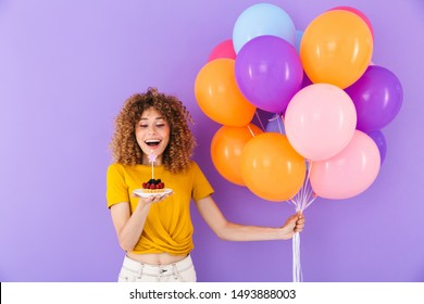 Image of happy young woman celebrating birthday with multicolored air balloons and piece of pie isolated over violet background
