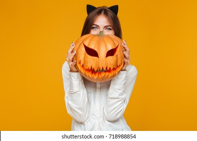Image of happy young woman dressed in crazy cat halloween costume over yellow background with pumpkin.