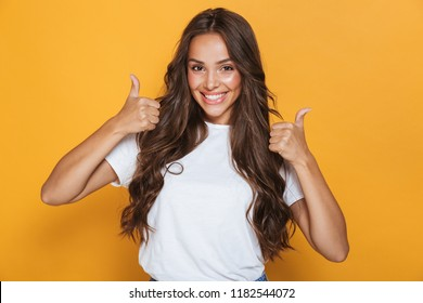 Image of happy young woman isolated over yellow background showing thumbs up gesture.