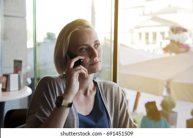 Image of happy young woman with short hair sitting at the table in cafe while using a cell phone. serious facial expression.
