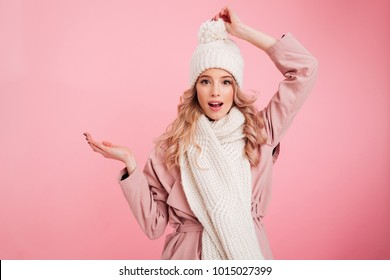 Image of happy young woman standing isolated over pink background wearing warm scarf. Looking camera.