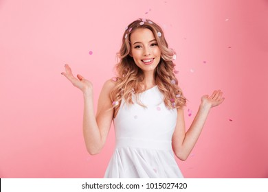 Image of happy young woman standing isolated over pink background over confetti. Looking camera.