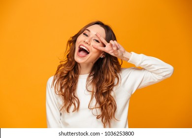 Image of happy young woman standing isolated over yellow background showing peace gesture. Looking camera.
