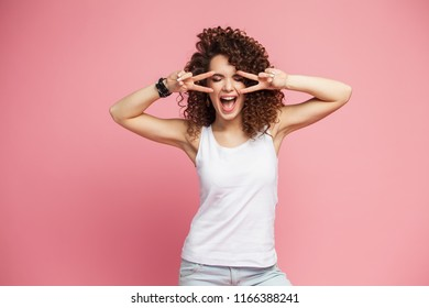 Image of happy young woman standing isolated over pink background showing peace gesture. Looking camera.