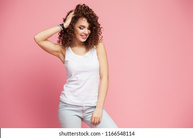 Image of happy young woman standing isolated over pink background. Looking camera pointing.