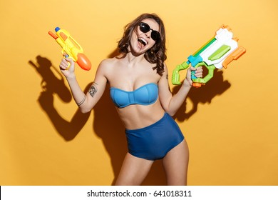 Image of happy young woman in swimwear isolated over yellow background holding toys water gun. Looking at camera.