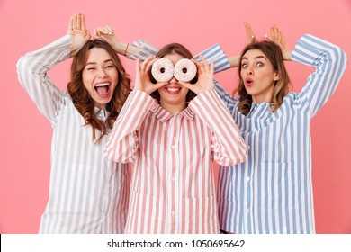 Image of happy and young women 20s with brown hair wearing leisure clothings having fun with sweet desserts donuts at slumber party isolated over pink background