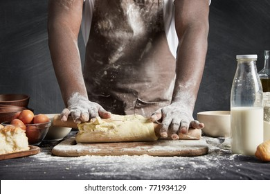 Image of hard working male cook or baker with dark skin wears apron, sheets well made dough, going to bake tart, isolated over black chalk background. Unrecognizable African American chef on kitchen