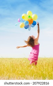 image of having fun romantic blond young lady holding air balloons running or walking in the field on summer blue sky outdoors copy space background
