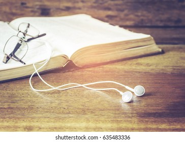 image of head phone connected to open holy bible with eye glasses on wooden table, conceptual image  christian listen to the voice of God