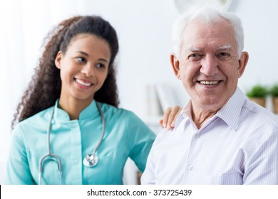 Image of helpful afroamerican caregiver and old man