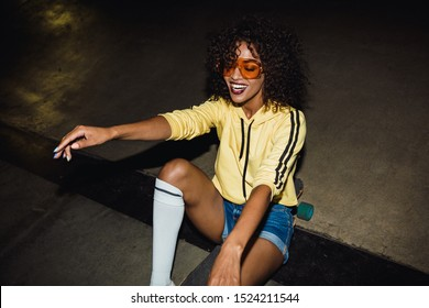 Image of hipster african american girl in streetwear smiling and riding on skateboard at night outdoors