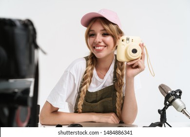 Image of hipster girl recording blog broadcast with microphone about new photocamera isolated over white wall in studio