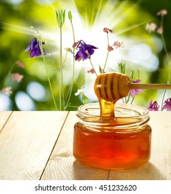 image of honey on the table against flowers background close up
