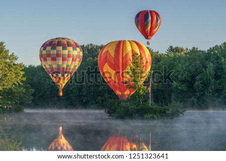 An image of hot air balloons performing skill maneuvers and an aerial ballet over a morning mist covered body of water gently touching the surface and taking flight during a balloon rally.
