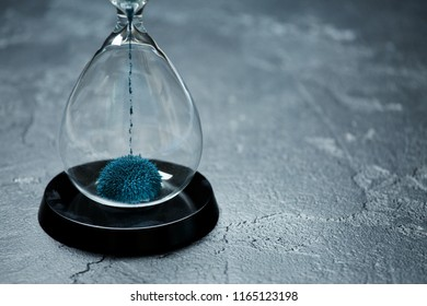 Image of hourglass with blue sand on black stone background,
