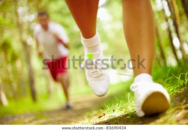 Image of human feet in sportshoes running down grass