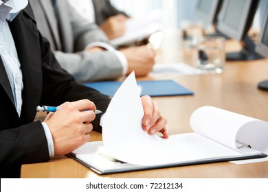Image of human hand holding pen and making notes at conference