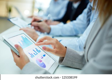 Image of human hand pointing at touchscreen in working environment at meeting