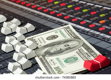 An image of a hundred dollar bill sitting on a mixing board.