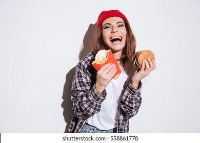 Image of hungry laughing woman dressed in shirt in a cage print wearing hat standing isolated over white background and holding fries and burger