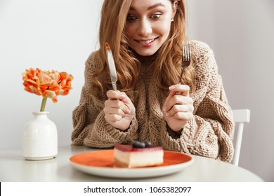 Image of hungry woman sitting at table and eating cake with appetite using fork and knife in coffee shop
