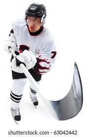 Image of ice-hockey player holding stick and standing ice