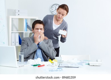 Image of ill businessman sneezing while his partner offering him good medicine in office