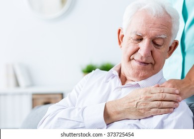 Image of ill positive senior man with support