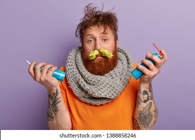 Image of ill red haired man has running nose, handkerchief in nostrils, wears knitted warm scarf on neck, holds aerosols, cures cold, has tattoo on arms stands over purple background. Seasonal disease
