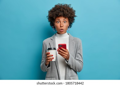 Image of impressed African American business lady holds paper cup and smartphone, receives shocking news, has tough conversation, gasps from surprisement, has red manicure, being late for work