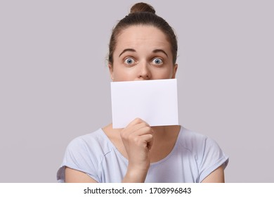 Image of impressed emotional energetic young lady with bun standing isolated over beige background, looking directly at camera, opening eyes widely, covering mouth with blank sheet of paper.