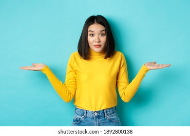 Image of indecisive asian woman shrugging shoulders, spread hands sideways and looking clueless at camera, standing indecisive against blue background