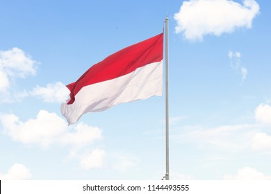 Image of Indonesia flag flying on the flagpole with blue sky background