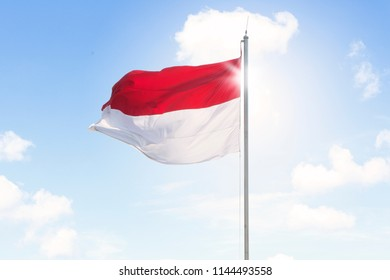 Image of Indonesia flag waving on a flagpole under blue sky