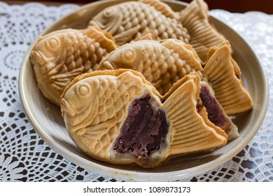 Image of inside the Taiyaki. Taiyaki, a fish-shaped sweet, is Japanese street snack sweets filled with red beans on a plate.