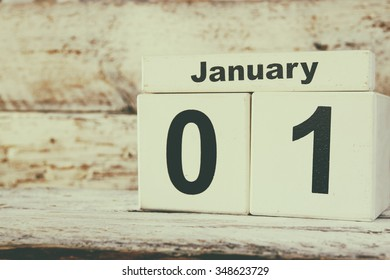 image of January First wooden vintage calendar on white background. retro filtered