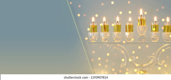 image of jewish holiday Hanukkah background with crystal menorah (traditional candelabra) and candles