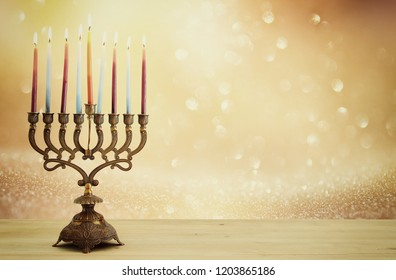 image of jewish holiday Hanukkah background with menorah (traditional candelabra) and candles over glitter shiny background