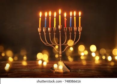 image of jewish holiday Hanukkah background with menorah (traditional candelabra) and burning candles. glitter overlay