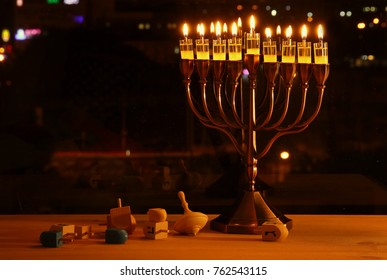 image of jewish holiday Hanukkah background with menorah (traditional candelabra) and burning candles in front of the window