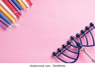 Image of jewish holiday Hanukkah  colorful candles, menorah (traditional Candelabra) on pink background.Flat lay.Copy space for text.