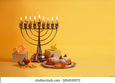 Image of Jewish holiday Hanukkah with menorah (traditional Candelabra), donuts and wooden dreidels (spinning top), doughnut, chocolate coins on a yellow background.