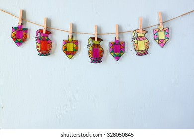 image of jewish holiday Hanukkah with Stained-glass colorful dreidels (spinning top) hanging on a rope over wooden background