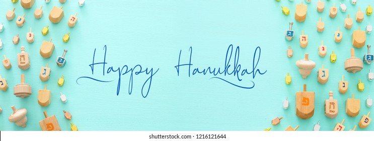 Image of jewish holiday Hanukkah with wooden dreidels colection (spinning top) over mint background